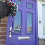 A purple Hathersage Formby front door with a hanging basket.