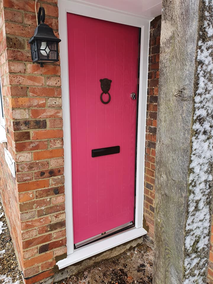 Traditional pink composite front door with black hardware